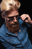 Man in blue shirt looking down and fxing his sunglasses Royalty Free Stock Photography