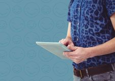 Man blue shirt mid section with tablet against blue emoji pattern. Digital composite of Man blue shirt mid section with tablet against blue emoji pattern stock photography