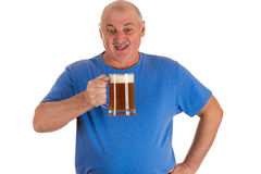 Man in a blue shirt with a mug of beer in hand Royalty Free Stock Images