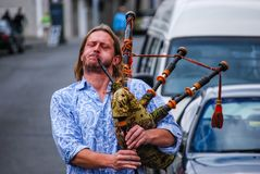 Man in blue shirt playing bagpipes in the street royalty free stock images