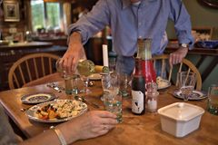 Man in blue shirt  pouring white wine to glass during dinner. In house. Posh home interior with homey atmosphere at lunch Stock Image