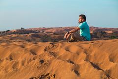 The man sits in bright day on a high barkhan crest in the desert. At a background the blue sky stock image