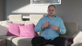 Man in blue shirt sitting in living room and trying to knit stock video footage