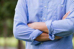 Man in a blue shirt standing. With arms crossed Royalty Free Stock Photo