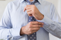 Man in blue shirt straightens his cufflinks Stock Images