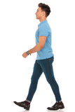 Man in blue shirt walking in isolated studio background Royalty Free Stock Photography