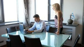 Man in blue shirt working on laptop at home. Pretty blonde woman comes up and flirts with him, stroking his head stock footage