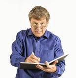 Man in blue shirt writes in his Stock Photo