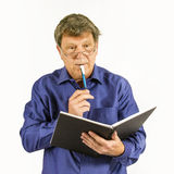 Man in blue shirt writes in his Stock Images