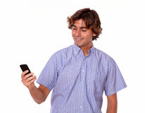 Man in blue shirts smiles while reading text. Stock Images