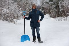 Man with blue snow shovel Stock Images