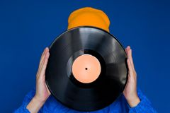 Man in a blue sport 90s style jacket and yellow hat holding vinyl record, man hides his face under vinyl disc. Young man in a blue sport 90s style jacket and royalty free stock images