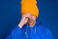 man in a blue sport 90s style jacket and yellow hat portrait ,man hiding his face under cap royalty free stock photography