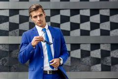 A man in a blue suit against a background of dark modern architecture. A stylish man in a blue suit on the background of a modern building stock photography