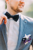 Man in blue suit with black bow tie, flower brooch, and classic texture pocket square, close up Royalty Free Stock Photography
