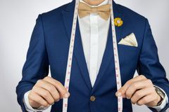 Man in blue suit bowtie, brooch, pocket square blue suit carry m Royalty Free Stock Images