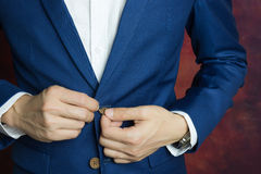 Man in blue suit, doing button. Man in blue suit two bottons, doing button royalty free stock photo