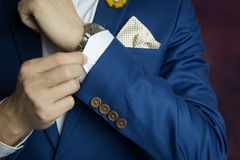 Man in blue suit, doing button. Man in blue suit two bottons, doing button, close up stock photo