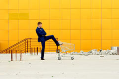 A man in a blue suit with an empty  shopping  cart. Stock Image