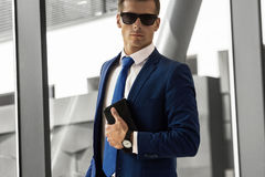 A man in a blue suit and glasses in a modern building royalty free stock images