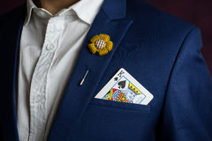 Man in blue suit with king spades. Man wearing blue suit, jacket and flower brooch, holding king spades in the pocket, casino concept Stock Photos