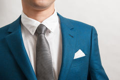 Man in blue suit. With silver necktie, white shirt and pocket square, close up royalty free stock photos