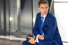 A man in a blue suit is sitting in a modern building. A handsome man in a blue suit and tie inside a modern building Royalty Free Stock Photos