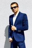 Man in blue suit and sunglasses standing stock image