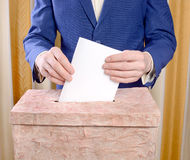 Man in a blue suit throws a ballot into the ballot box Royalty Free Stock Photography
