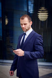 Man in a blue suit touching a smartphone. Businessman touching smart phone standing outside business center Stock Image