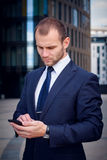 Man in a blue suit touching a smartphone. Businessman touching smart phone standing outside business center Royalty Free Stock Image