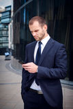 Man in a blue suit touching a smartphone. Businessman touching smart phone standing outside business center Stock Images