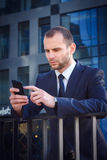 Man in a blue suit touching a smartphone. Businessman touching smart phone standing outside business center Stock Photo