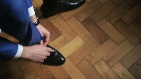 Man in blue suit tying black leather shoes preparing for formal event stock footage