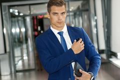 A man in a blue suit is walking along a modern building. A handsome man in a blue suit and tie inside a modern building Stock Image