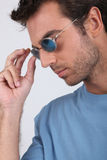 Man with blue sunglasses. Profile shot of a man with blue sunglasses Stock Image