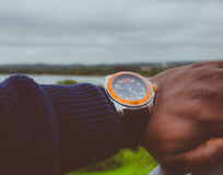 Man in Blue Sweater Black Strap Silver and Orange Round Analog Watch Showing 4:47 Stock Photo