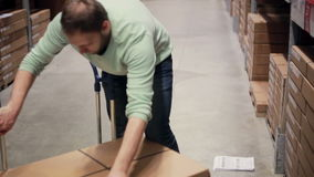 A man in a blue sweater is taking boxes from the shelf, putting them on the trolley in a storage warehouse stock video
