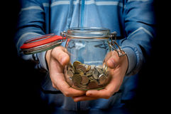 Man in blue sweatshirt holding money jar with coins. On black background royalty free stock image