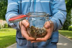 Man in blue sweatshirt holding money jar with coins. On the street stock image