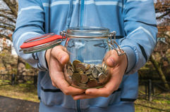 Man in blue sweatshirt holding money jar with coins. On the street stock photography