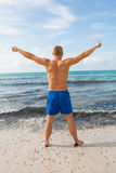 Man in blue swim shorts in the beach Royalty Free Stock Image