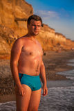 man in blue swimming trunks standing on beach Stock Photography