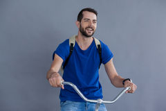 Man in blue t-shirt and back posing sitting on a bicycle. Man in blue t-shirt and back sitting on a bicycle against grey background Stock Photo