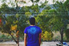 Man in Blue T Shirt Black Tattoo Arm in Front of Green Trees Under Blue Sky Stock Photos