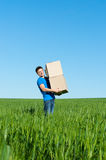 Man in blue t-shirt carrying boxes Royalty Free Stock Images