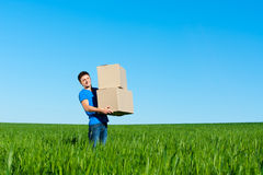 Man in blue t-shirt carrying boxes Royalty Free Stock Photos