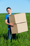 Man in blue t-shirt carrying boxes Stock Photo
