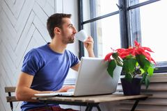A man in a blue t shirt drinks coffee. A man in a blue t shirt drinks coffee and working with laptop Stock Photography