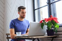 A man in a blue t shirt drinks coffee. A man in a blue t shirt drinks coffee and working with laptop Stock Images
